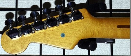 Covered hexagonal tuning machines of the Squier SST-30. The